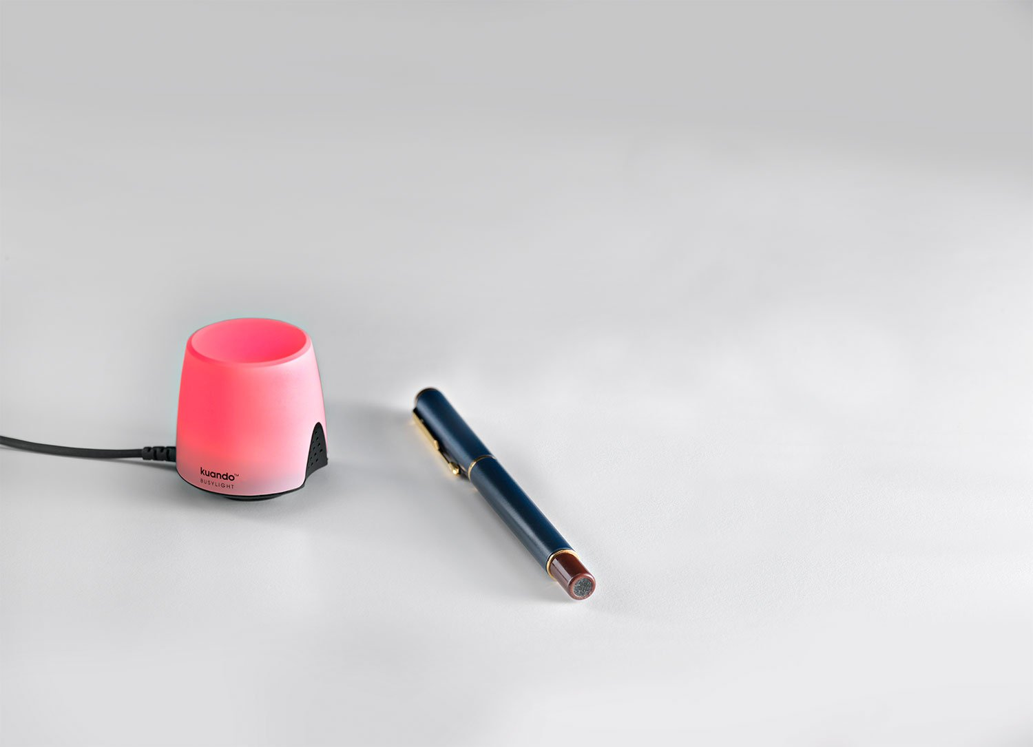 Red kuando busylight omega next to a pen